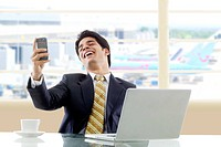 Businessman laughing after reading an sms
