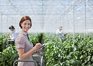 Woman writing on clipboard in greenhouse
