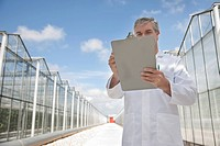 Scientist writing on clipboard outside greenhouses