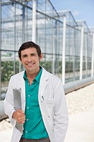 Scientist walking outside greenhouses