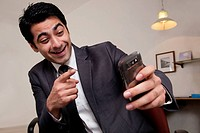 Businessman pointing at his mobile phone
