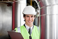 Businessman in safety gear examining pipes
