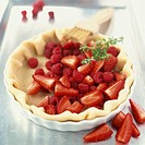 Preparing a strawberry and raspberry tart