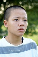 Depressed asian teen girl with shaved head