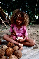 A young Fijian girl cutting our the white meat of a coconut. When dried, the coconut meat becomes copra.