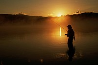 The morning sun comes up behind a fly fisherman in Lake Dillon.