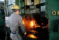 An automotive factory worker works with a hot, glowing part in the forge at the Tremec plant. Tremec is a Mexican_owned manufacturer of standard trans...