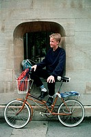 An Oxford student rests in a window with his bicycle and backpacks.