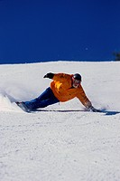 A snowboarding touches the snow after making a tight turn