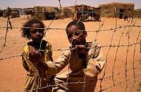 Children displaced by famine stare through a fence at a Khartoum refugee camp, Sudan.
