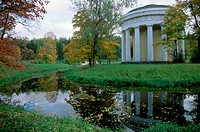 A stream flows passed the Temple of Friendship standing amid colorful autumn trees at Pavlovsk, Russia.
