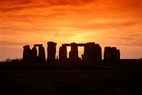 Sunset silhouettes Stonehenge, the ancient stone ring on Salisbury Plain.