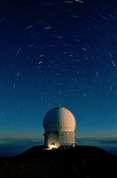 In a time_lapse photograph, stars appear to circle the Canada_France_Hawaii Telescope on Mauna Kea.