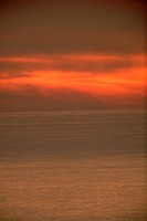 Clouds glow a dull orange after an annularly eclipsed Sun has sunk into the Pacific.