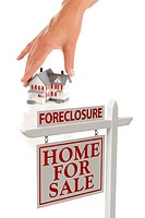 Womans Hand Choosing Home with Foreclosure Real Estate Sign