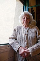 Portrait of old woman posing by the window
