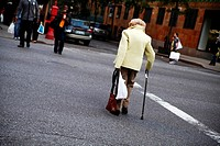 Elderly Woman with a cane and shopping bag, crossing a busy street