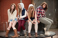 A group of 13 year old teenage girls, looking bored moody with attitude, sitting on a bench UK