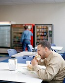 Man Eating Sandwich in Office Cafeteria