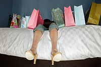 Woman Lying on Bed with Shopping Bags