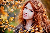 The red_haired girl in autumn leaves