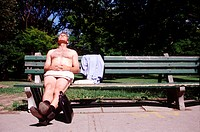 Naked businessman on a park bench
