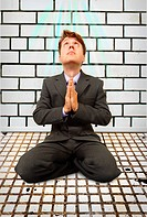 Comic businessman on knees praying