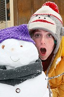 freckled girl in sock-monkey hat and yellow parka, standing with mouth open behind the snowman she built - snowman has purple hat, grey scarf