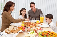 An attractive happy, smiling family of mother, father, son and daughter eating salad and pizza at a dining table, The mother is serving a slice of piz...