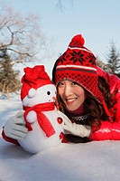 Woman in warm clothing posing with snowman in snow