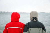 two people in jacket with hood on the river background