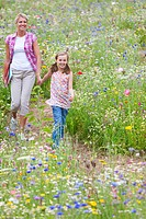 Mother and daughter holding hands and walking in wildflower field
