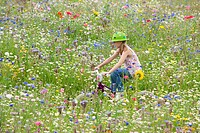 Girl riding bicycle in wildflower field