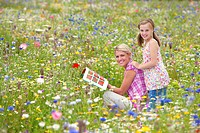 Mother and daughter looking at book in wildflower field