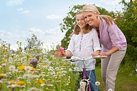 Mother and daughter with bicycle in wildflower field