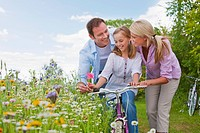 Family with bicycle in wildflower field