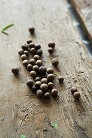 Black peppercorns on a wooden surface