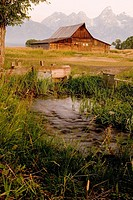 Barn with stream in front of the Tetons, near Jackson in Wyoming