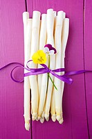 A bunch of white asparagus on a purple wooden surface