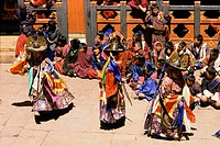 Bhutanese dancers wearing elaborate black and gold hats perform at the Paro Tsechu Festival.