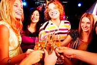 Portrait of group of happy young people toasting at party