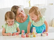Mother and daughters 2_3 playing with letter blocks