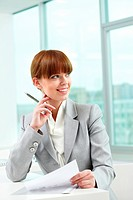 Portrait of attractive office worker looking aside in office