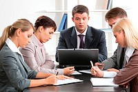 Photo of business group sitting at workplace and working with papers