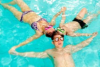 Photo of parents and their son in goggles holding by hands in water