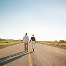 Mid adult couple walking along empty road