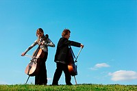 Two violoncellists play on grass against sky