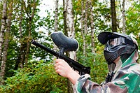 paintball player shoots aside in forest
