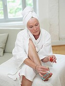 Senior woman painting toenails, close up
