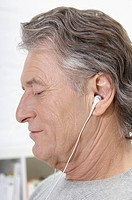 Germany, Hamburg, Senior man listening music, close up (thumbnail)